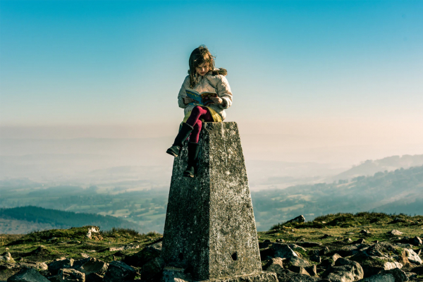 girl on top of a mountain reading a story